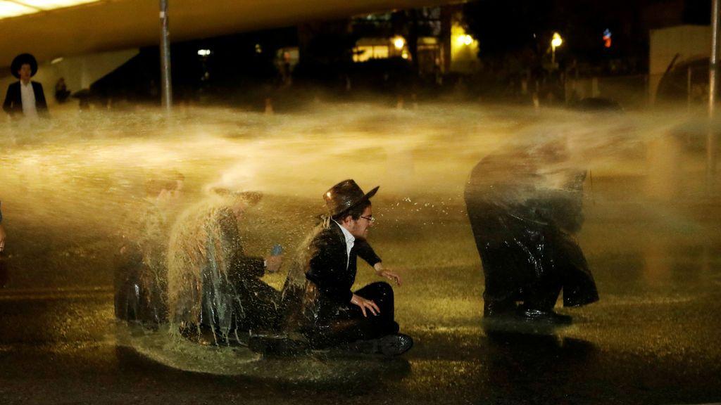 Hombres judíos israelíes ultraortodoxos reciben un chorro de agua durante una protesta contra la detención de un miembro de su comunidad en Jerusalén, Israel