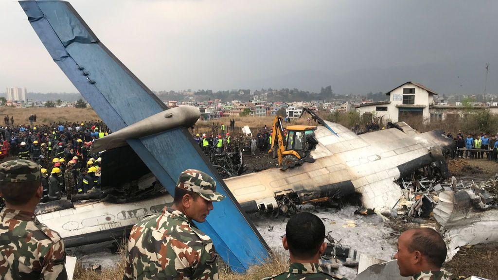 Los trabajadores de rescate operan entre los restos de un avión accidentado en el aeropuerto de Katmandú, Nepal