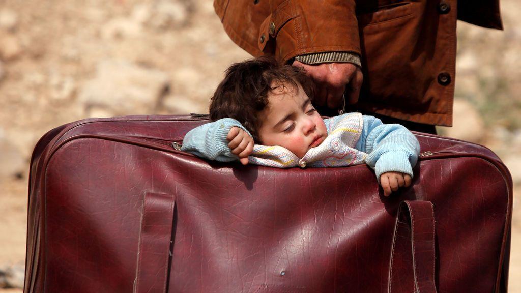 Un niño duerme dentro de una maleta en la aldea de Beit Sawa, al este de Ghouta, Siria