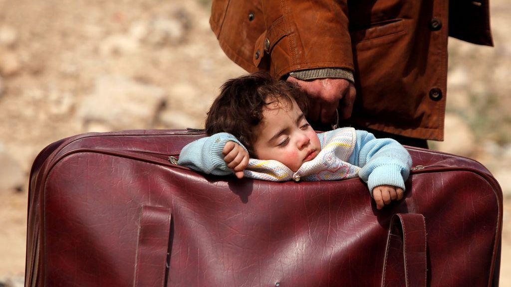 Un bebé duerme en el interior de una maleta en el pueblo sirio de Beit Sawa