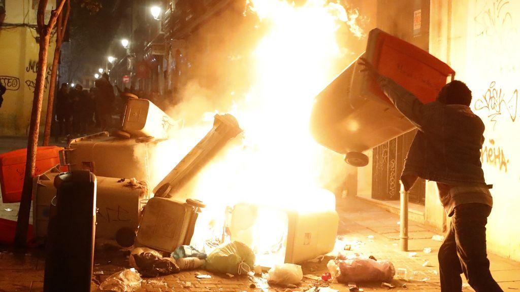 Contenedores incendiados en la calle Mesón de Paredes con la calle del Oso, en el barrio de Lavapiés de Madrid