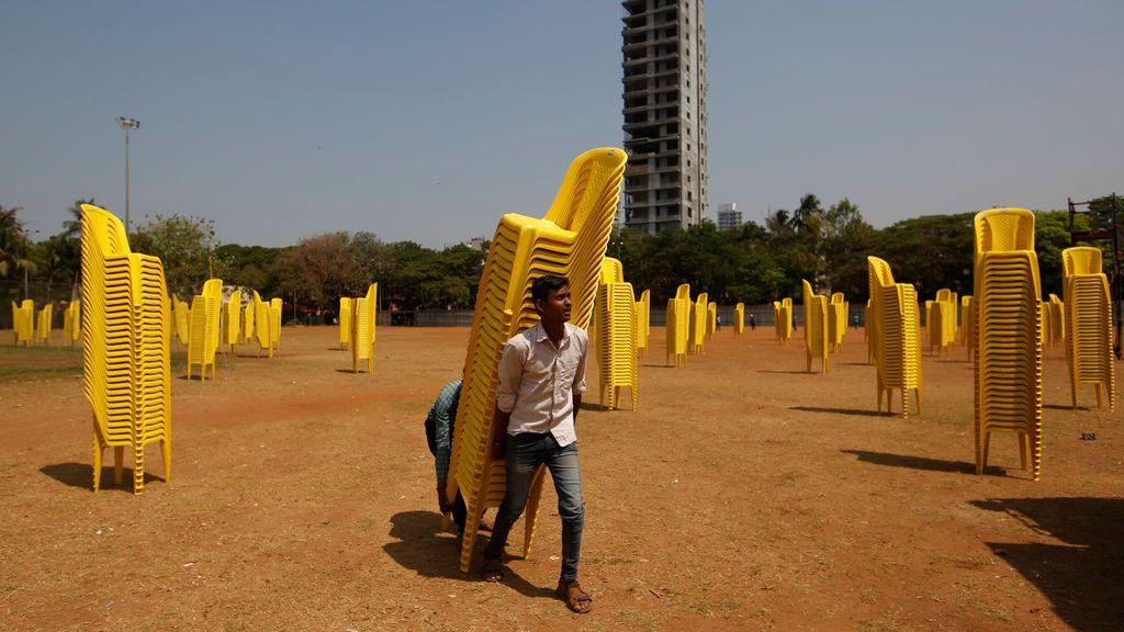 Los trabajadores llevan sillas de plástico después de una concentración política en Mumbai, India