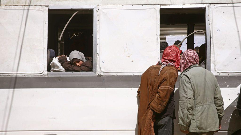 Una niña mira por la ventanilla de un autobús durante la evacuación de la sitiada ciudad de Douma, Ghouta Oriental, en Damasco, Siria