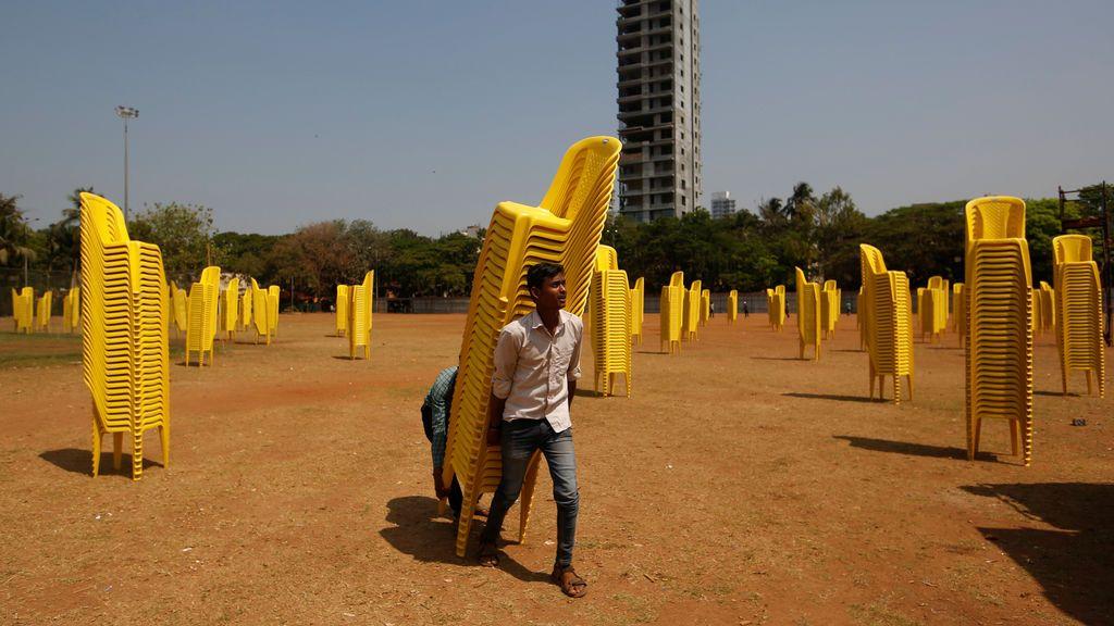 Trabajadores llevan sillas de plástico después de una concentración política en Mumbai, India