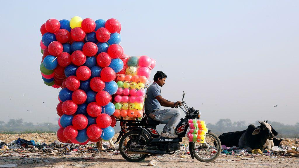 Un hombre translada en moto bolas de colores