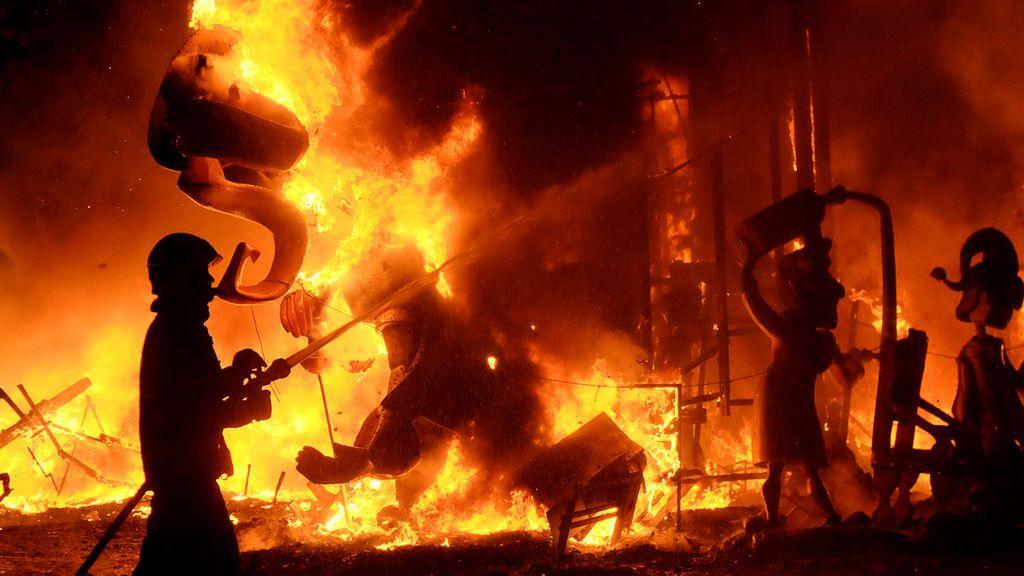 Un bombero apaga el fuego de las figuras de una falla durante el final de las Fallas, que da la bienvenida a la primavera, en Valencia
