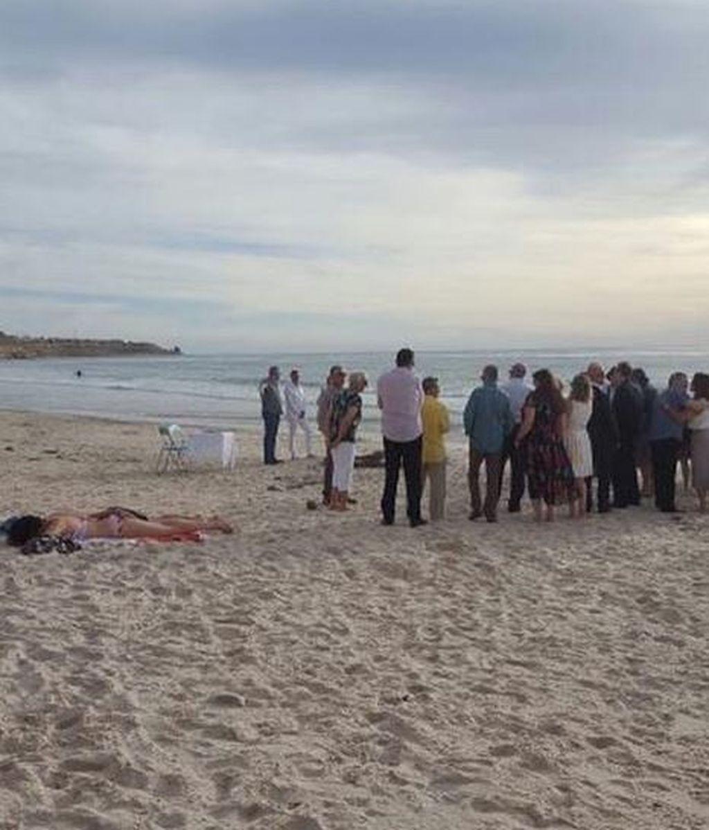 Se niega a moverse mientras toma el sol al lado de una boda en la playa