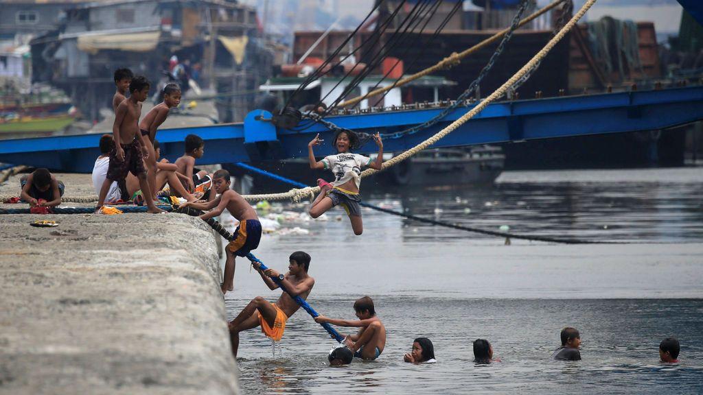 Varios niños se bañan en la bahía de Manila