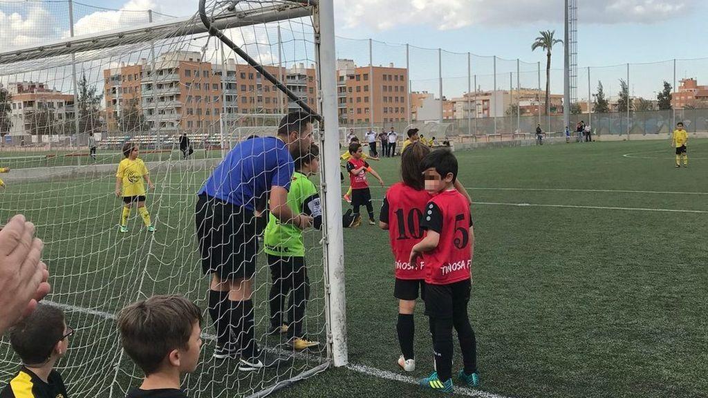 Un árbitro para un partido de prebenjamines para enseñar al portero cómo colocar la barrera