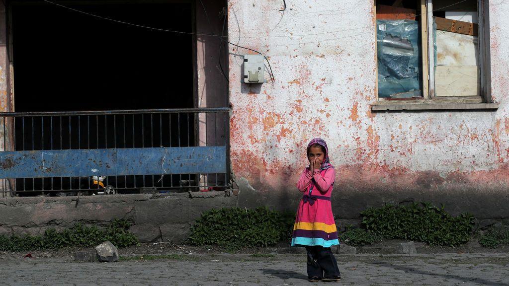 Una migrante afgana se ríe frente a su casa