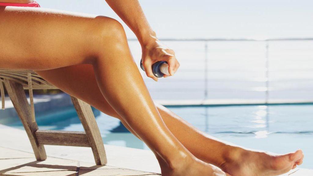 woman-using-spray-tan-on-legs