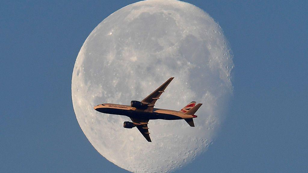 Impresionante fotografía el vuelo de un avión frente a la luna