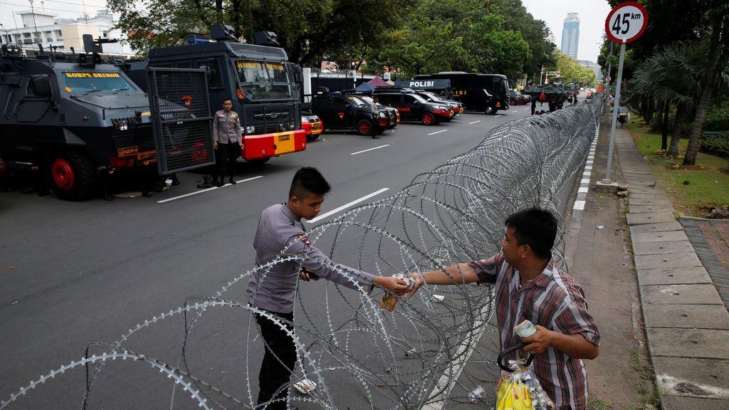 Un policía indonesio compra un refresco mientras hace guardia