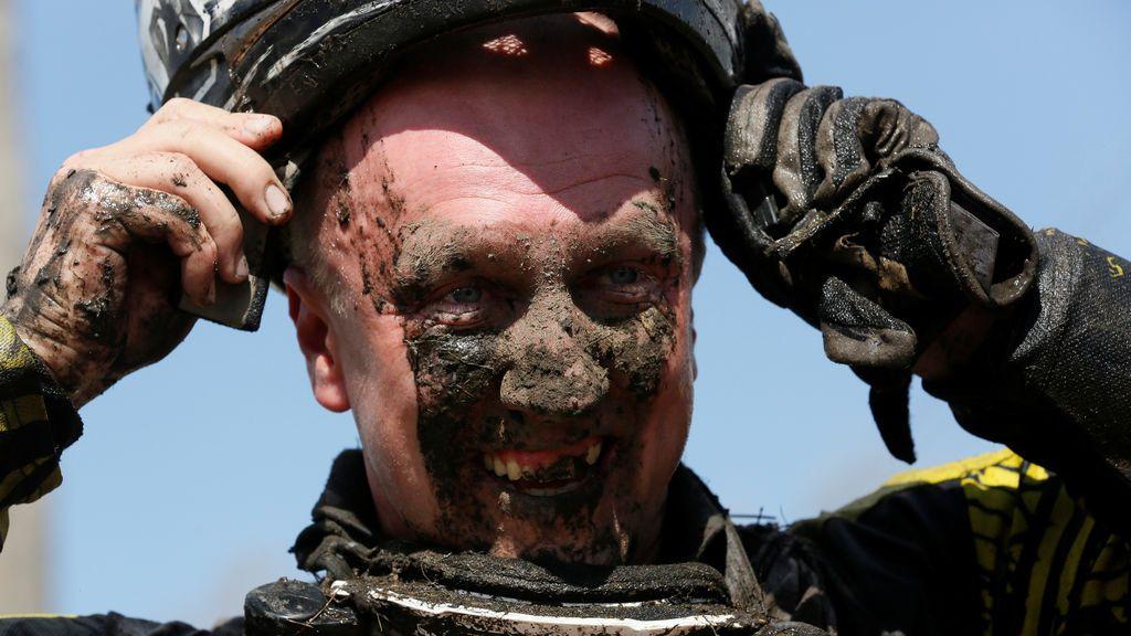 Un participante de una carrera de aficcionados de quad se quita el casco