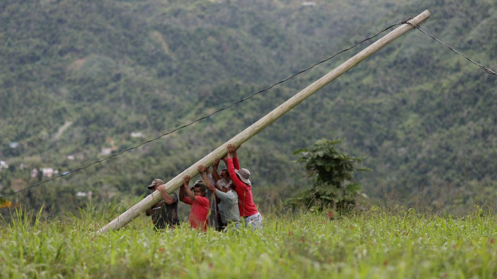 Varios hombres recolocan un poste eléctrico en Puerto Rico