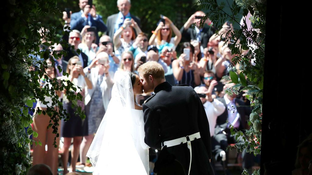 El matrimonio se besa ante las personas que les esperaban a la salida de la capilla de San Jorge