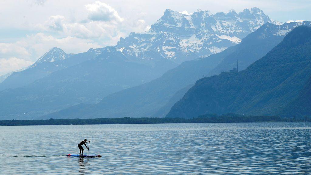 Un hombre rema en un lago suizo