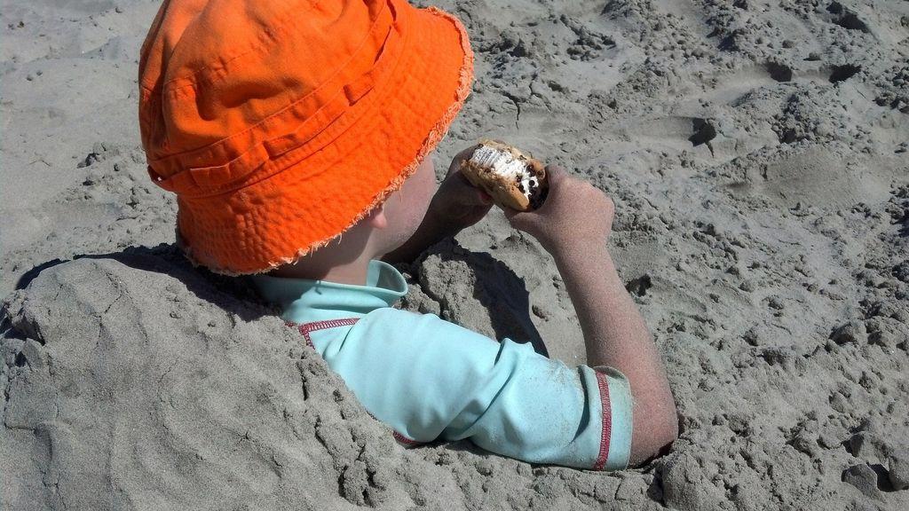 Niño comiendo en la playa