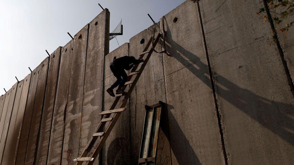 Un palestino cruza el muro para llegar a la oración