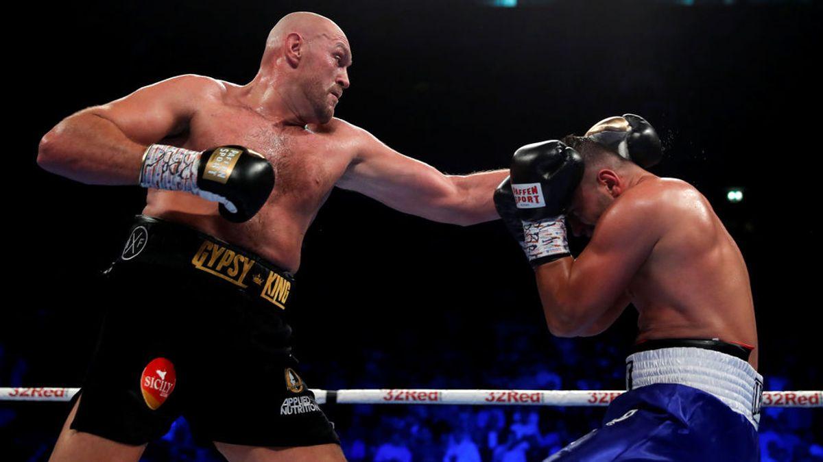 Dos boxeadores detienen su combate para ver una pelea multitudinaria entre los aficionados