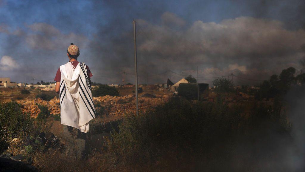 Un hombre reza antes de ser evacuado en Cisjordania