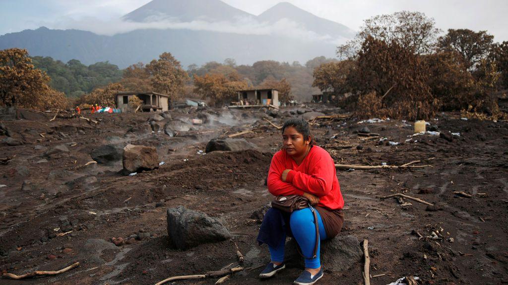 Una mujer mira cómo retiran la ceniza del volcán Fuego