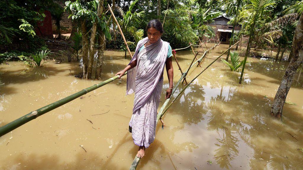 Una aldeana pasa por una zona inundada en India