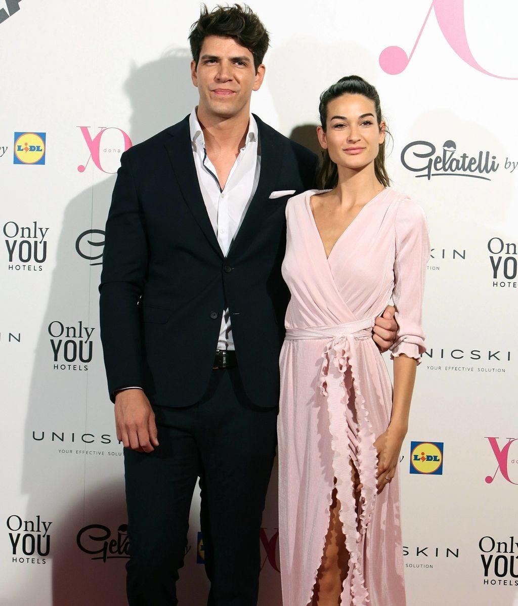 Diego Matamoros, en traje de chaqueta negro, junto a su novia, Estela Grande, con vestido rosa pastel de abertura lateral