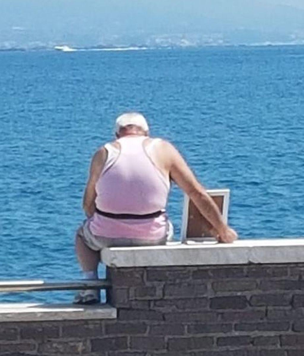 Un hombre lleva el retrato de su esposa muerta al mar