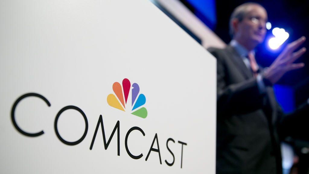 Al fondo de la imagen, el presidente y director ejecutivo de Comcast, Brian Roberts.