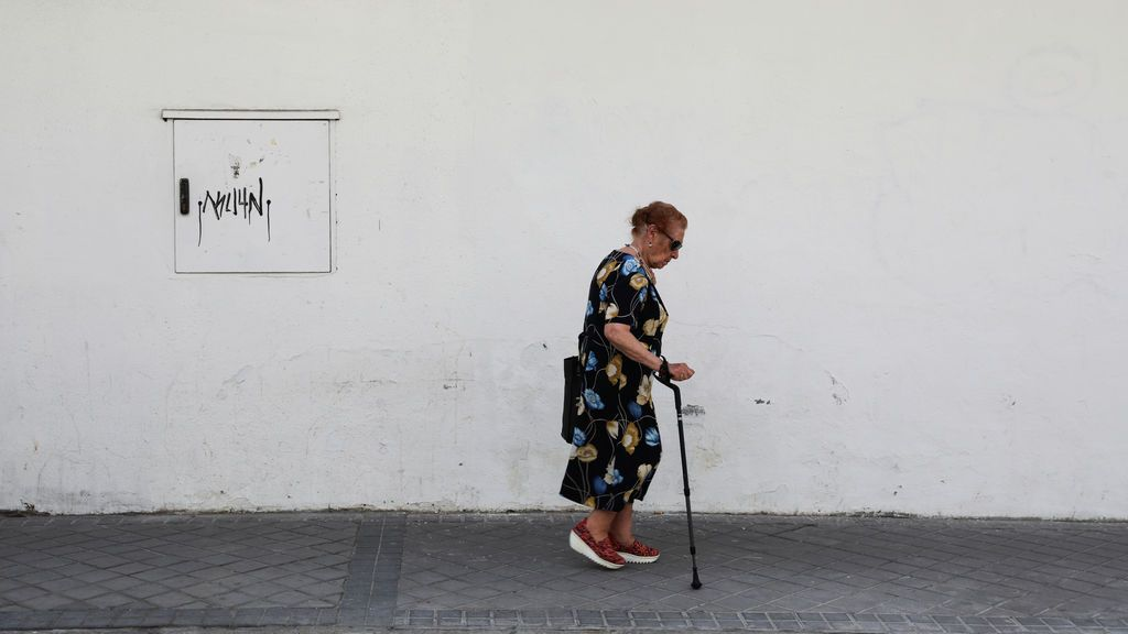 Un mujer mayor camina por una calle de Madrid