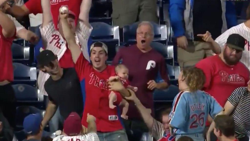 El arriesgado gesto de un padre en el béisbol: coger una pelota al vuelo con su hijo en brazos