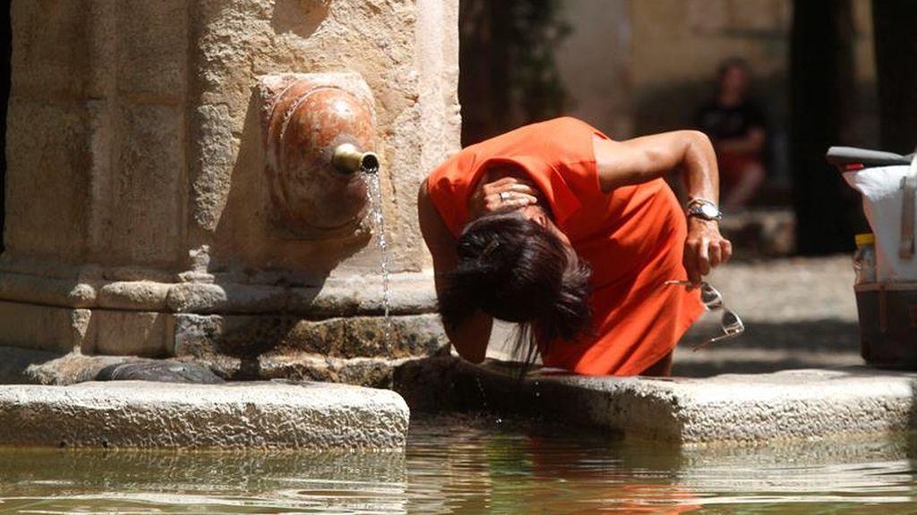 Una mujer se refresca en una fuente en Córdoba