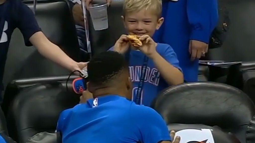 Su ídolo le ofrece una de sus zapatillas a cambio del trozo de pizza que se está comiendo, pero el pequeño se queda con ambas cosas