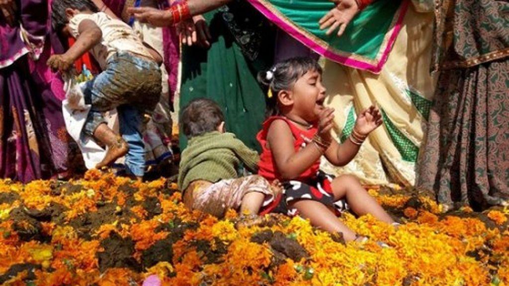 Rebozar a los niños en excrementos de vaca para atraer la buena suerte, un raro ritual en la India