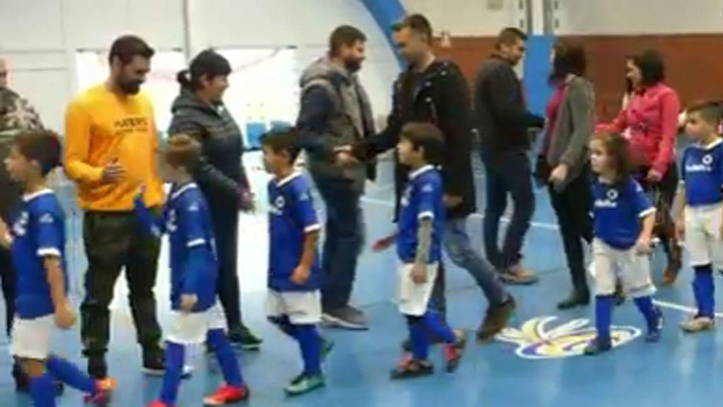 Padres e hijos saltan al campo de la mano en un partido de prebenjamines en Asturias