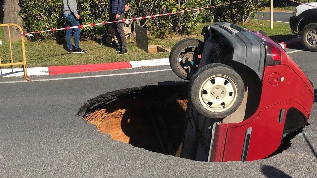 El asfalto se traga un coche en una rotonda de Huelva