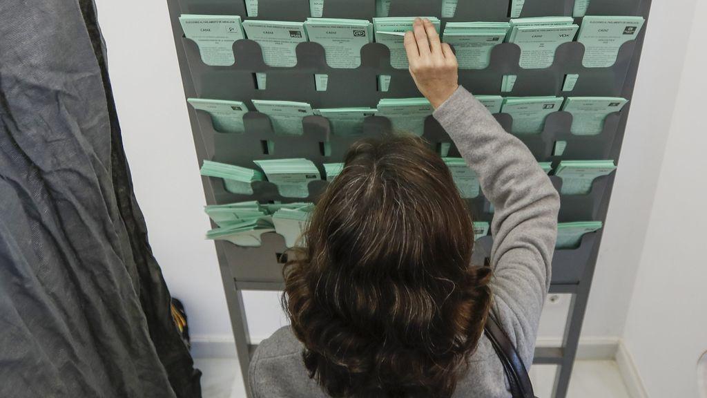 Una votante escoge la papeleta para elegir a su candidato hoy en el colegio electoral ubicado en la biblioteca de Sanlúcar de Barrameda