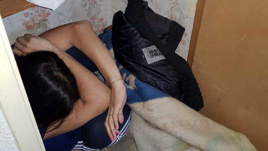 Una víctima de violencia machista se esconde de su agresor en un armario bajo un montón de mantas