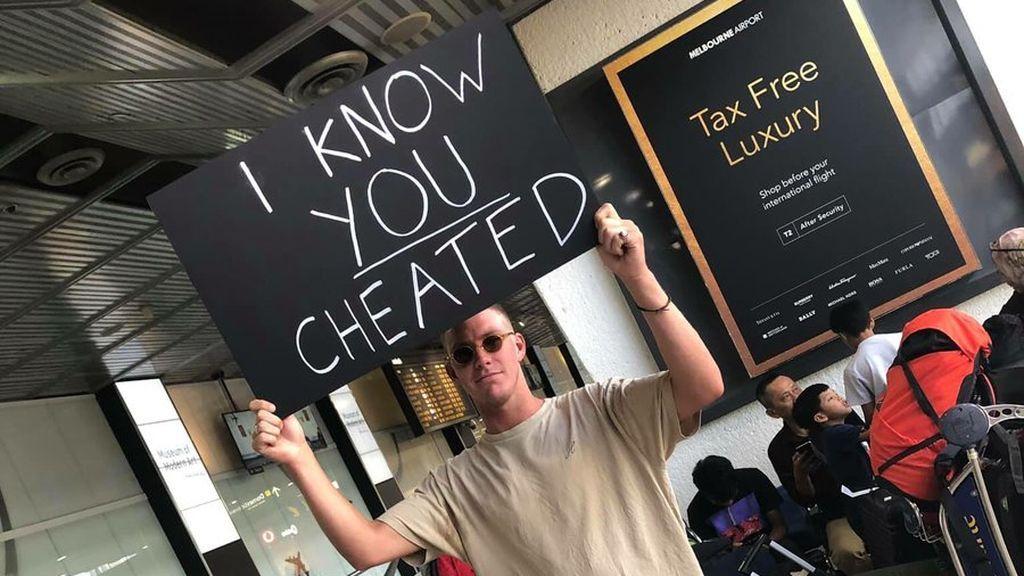 """Espera a su pareja en el aeropuerto con un cartel: """"Sé que me has engañado"""""""