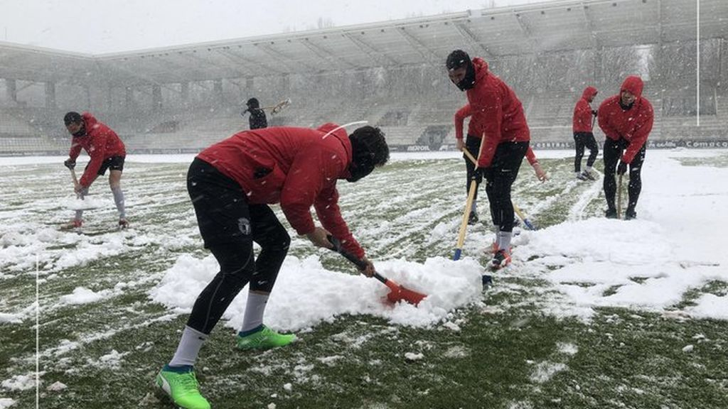 Los jugadores del Burgos C.F. calientan recogiendo la nieve que ha invadido su estadio