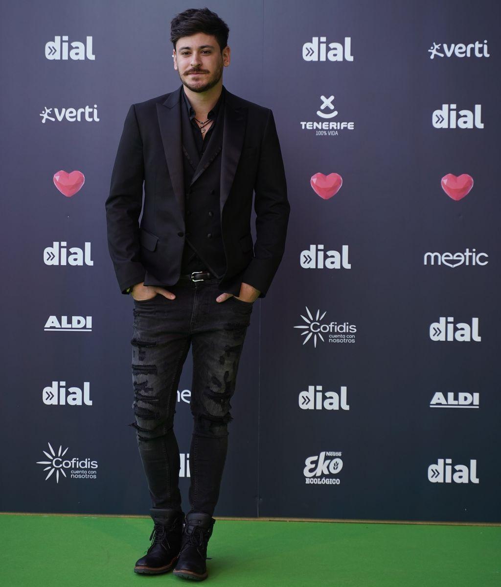 Luis Cepeda combinando chaqueta formal y pantalones con rotos