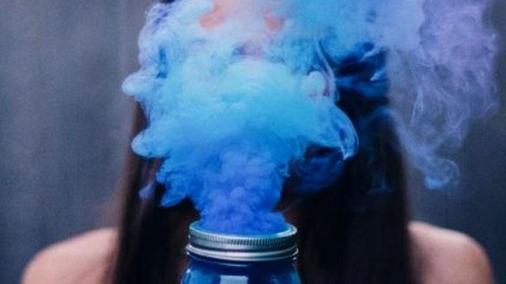 mujer-sujetando-tarro-del-que-sale-humo-azul-1