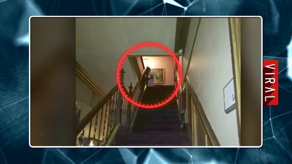 La espeluznante aparición de una dama de blanco al final de una escalera