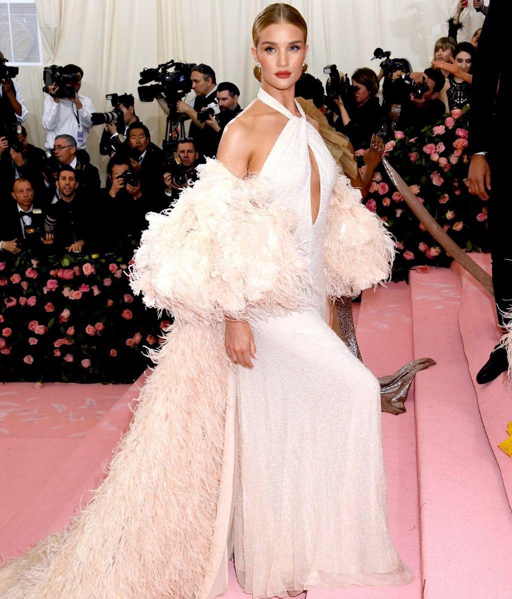 Rosie Huntington-Whiteley con vestido blanco y capa de plumas de Oscar de la Renta