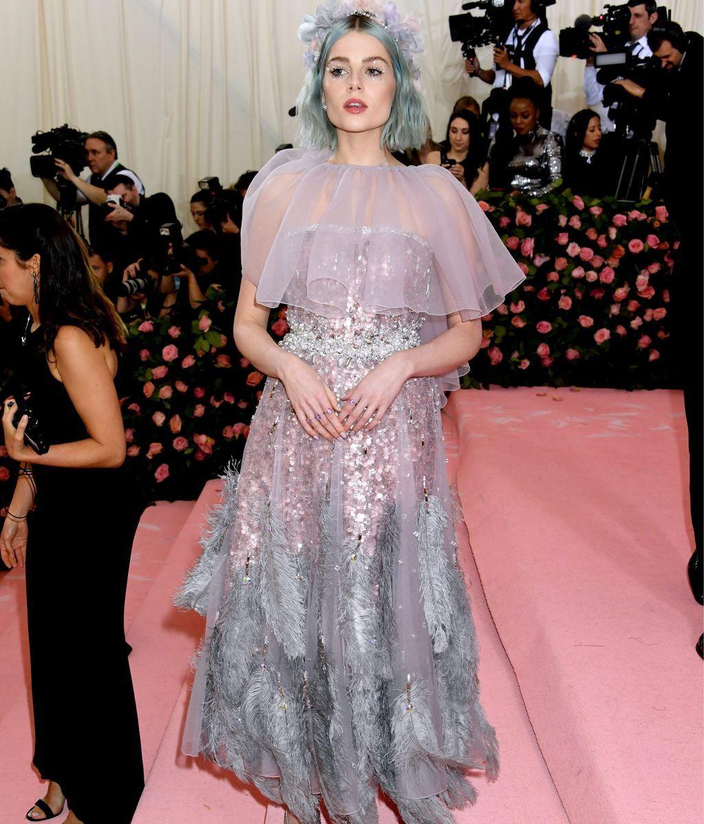 Lucy Boynton con el pelo azul cielo y un vestido de plumas y lentejuelas