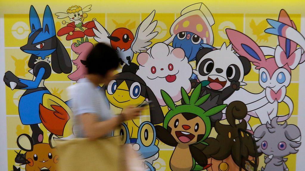 Una mujer camina frente a una imagen de personajes de Pokémon