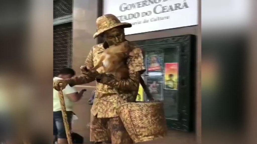 Un perro posa como una estatua junto a su dueño en un centro comercial de Brasil