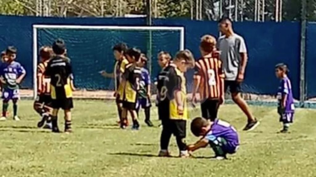 Un niño da una lección de deportividad al agacharse para atarle los cordones a un jugador del equipo rival