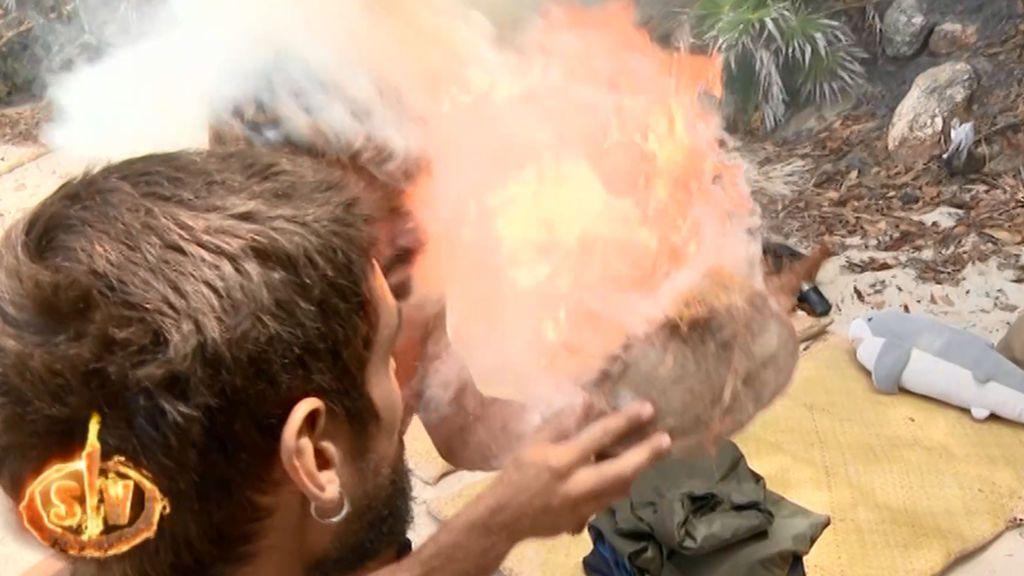 Albert, a punto de quemarse el pelo y la cara al avivar el fuego